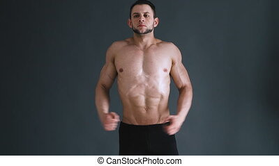 bodybuilder flexing his muscles at studio, dark grey...
