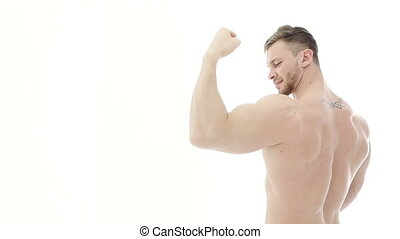 Bodybuilder flexing his muscles. Athlete demonstrates biceps...