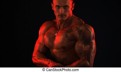 bodybuilder flexing his muscles in red light