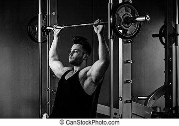 bodybuilder guy in gym with heavy weights  monochrome