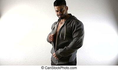 Bodybuilder handsome man undressing, taking off jacket