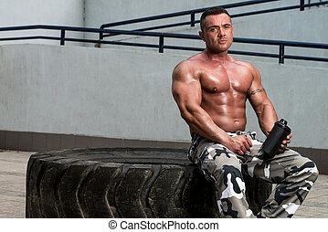 bodybuilder, het rusten, en, drinkt, proteine verwiken, na, het uitoefenen, in, gym