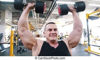 Bodybuilder in a black tank top performs a dumbbell shoulder...