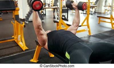 Bodybuilder in a black tank top pumping his chest muscles....