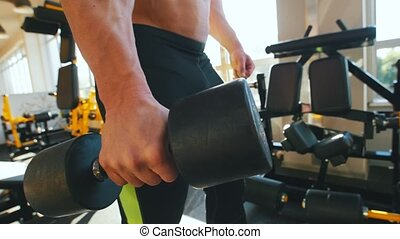 Bodybuilder in a black tank top pumping his shoulder muscle. Mid shot