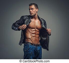 Bodybuilder in blue jeans and black jacket.