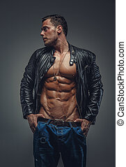 Bodybuilder in blue jeans and black jacket. - Young...
