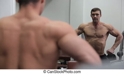Bodybuilder in front of the mirror shows his huge muscles. Young man athlete takes various poses, showing relief and profitable conceived shoulder muscles, chest muscles, abdominal muscles, biceps and triceps, his face expresses enjoyment and satisfaction with his appearance and his success. He will...