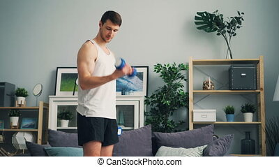 Bodybuilder in sportswear working out with dumbbells at home...