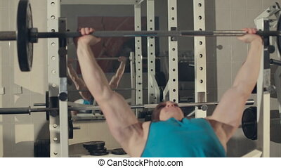 Bodybuilder in the exercise machine  build muscles with a barbell