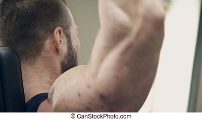 Bodybuilder in the weight belt lifting heavy dumbbells hands. Bearded man intensively conducts training for formation of a relief on muscles of hands. Skin of an athlete has numerous injuries on the skin, since one of the main factors triggering acne is the hormonal background of the body, and in ...
