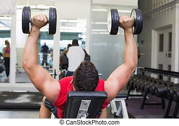 Bodybuilder lying on bench lifting dumbbells