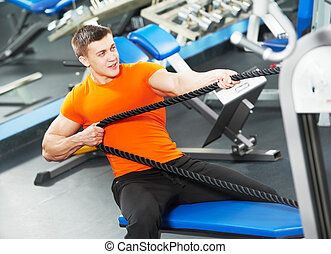bodybuilder man doing exercises in fitness club