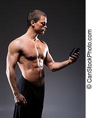 Bodybuilder man with a bottle of sport supplements