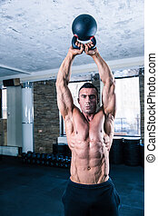 Bodybuilder man workout with kettle ball