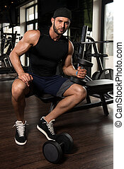 Bodybuilder Performing Biceps Curls With Dumbbells