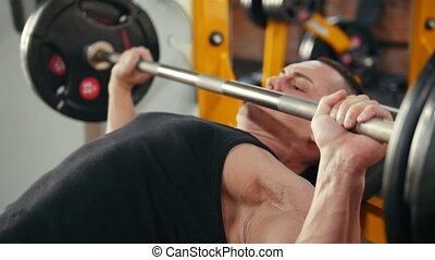 Bodybuilder performing incline barbell press exercise on a bench in the gym. Close up