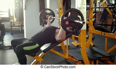 Bodybuilder performing incline barbell press exercise on a bench in the gym.