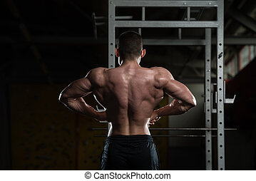 Bodybuilder Performing Rear Lat Spread Pose - Young Man...