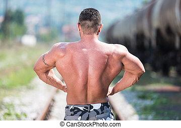 BodyBuilder Posing At The Railroad