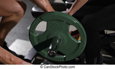 bodybuilder puts weight on the barbell. Communicates with a pretty athlete