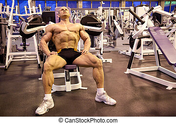 bodybuilder rests in training room