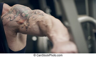Bodybuilder shakes his biceps on arm with a tattoo on the simulator.