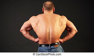 Bodybuilder shows his muscular body from behind and then turn around lit