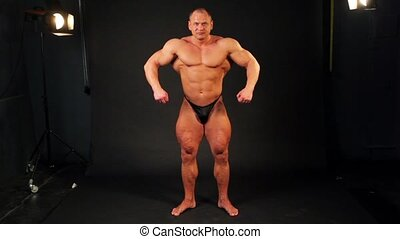 Bodybuilder shows his muscular body from behind and then turn around in studio