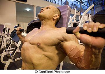 bodybuilder sideways doing weightlifting in gym