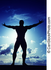 Bodybuilder silhouetted against the sky