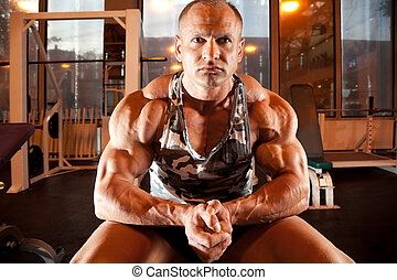 bodybuilder sits in training room