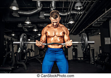 Bodybuilder sportsman working out with a barbell in gym, doing biceps training.