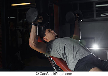 bodybuilder training in the gym: chest - dumbbell bench press.