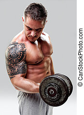 Bodybuilder with a tattoo lifting weights, closeup