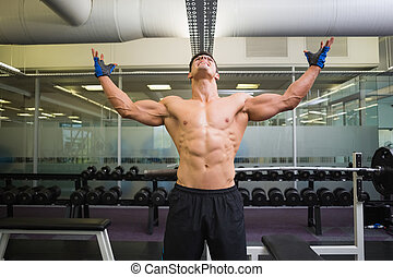 Bodybuilder with arms raised in gy