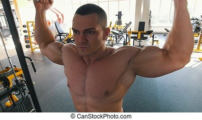 Bodybuilder with bare torso performs an overhead cable curl exercise in the gym