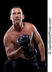 bodybuilder with dumbbell, shot on a black background
