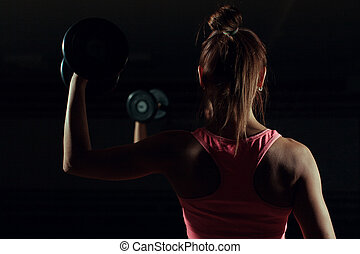 Bodybuilder woman with dumbbells on a dark background.