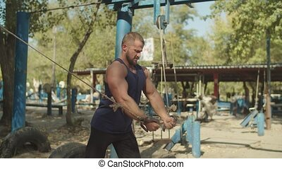 Bodybuilder working out with cable crossover in gym