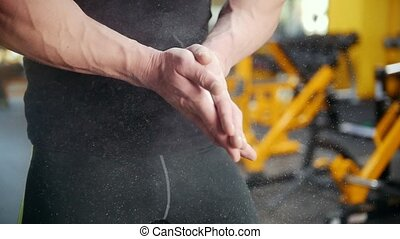 Bodybuilder's hands covered in chalk make clap in the gym....