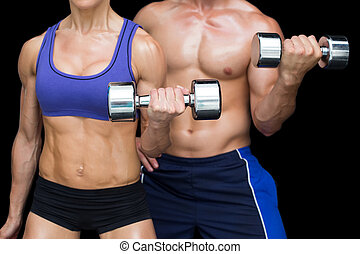 Bodybuilding couple posing with large dumbells on black ...