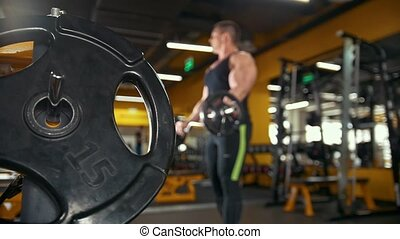 Bodybuilding in the gym - muscular man training his biceps...