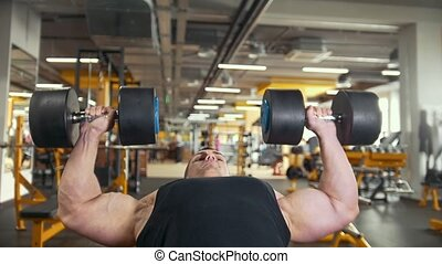 Bodybuilding in the gym - young muscular man performs training for biceps with dumbbells