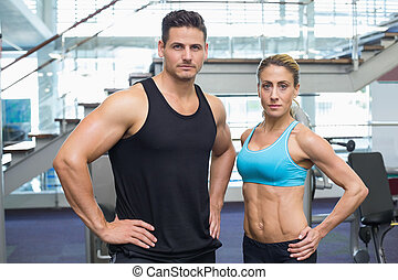 Bodybuilding man and woman frowning at camera
