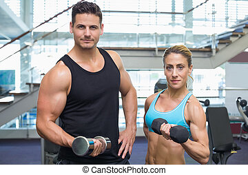 Bodybuilding man and woman holding dumbbells smiling at camera
