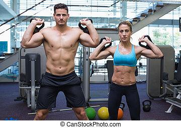 Bodybuilding man and woman lifting kettlebells looking at camera