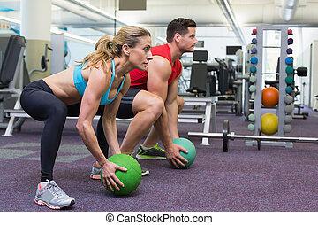 Bodybuilding man and woman lifting medicine balls doing ...