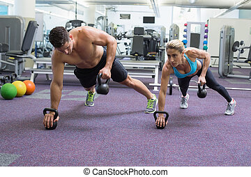Bodybuilding man and woman lifting kettlebells in plank...
