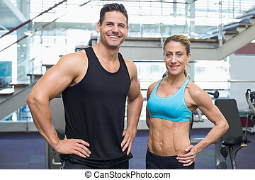 Bodybuilding man and woman smiling at camera